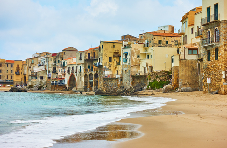 Sandy beach and old houses by the sea in Cefalu, Landmark and seaside resort in Sicily, Italy