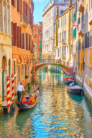 Venetian canal with gondola on sunny summer day, Venice, Italy
