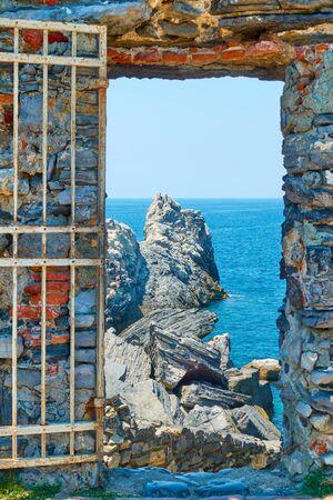 The sea and rocks through the ancient doorway near Church of St. Peter in Porto Venere (Portovenere) on Ligurian coast, La Spezia, Italy Landscape, seascape Reklamní fotografie - 129637670