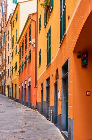 Perspective of old uphill street with yellow-orange picturesque houses in Genoa (Genova), Italy