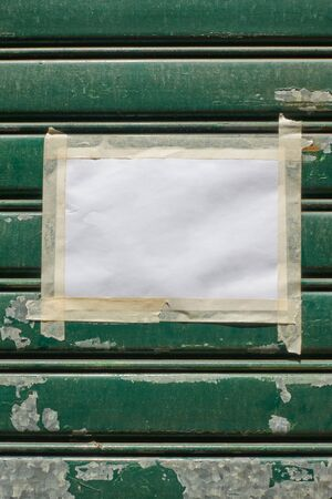 Blank paper with scotch tape on the door closed by roller shutter -- mock-up,  background and space for your own text