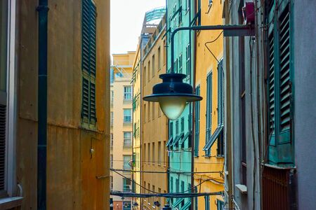 Genoese narrow old street with old street light on the wall, Genoa, Italy Reklamní fotografie - 129637320
