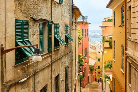 Perspective of the old downhill street leading to the Genova port, Genoa, Liguria, Italy Reklamní fotografie - 129637364