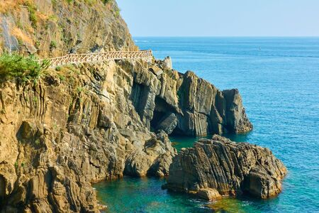 Rocky coast near Riomaggiore with the Love Road (Via dellAmore) in Cinque Terre, Italy. Stock Photo