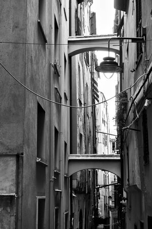 Old narrow street and houses with buttresses, Genoa, Italy. Black and white image