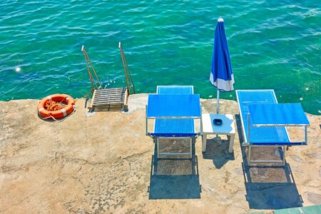 Vacante beachchairs next to the sea at seaside resort on sunny summer day Reklamní fotografie - 129636348