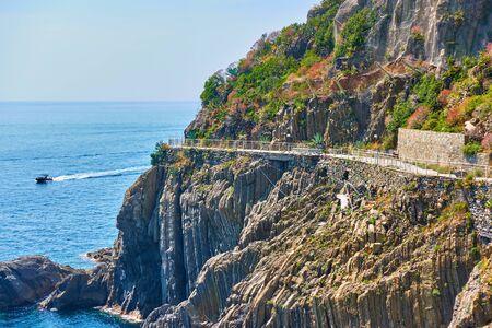 Rocky coast near Riomaggiore with closed Love Road (Via dellAmore) in Cinque Terre, Italy.