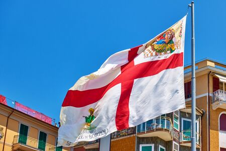 Flag of Genoa (Genova) city in the wind, Liguria, Italy Reklamní fotografie - 129636352