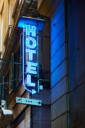 Blue neon hotel sign with arrow on the wall close-up Reklamní fotografie - 129636355