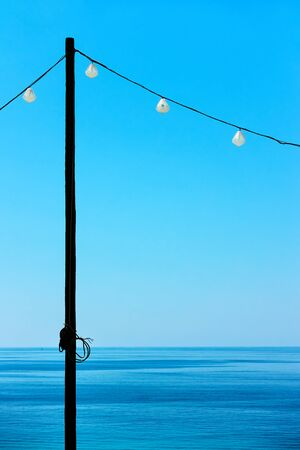 Seascape with sea horizon, clear blue sky and decorative string of holiday lights - Minimalistic background with space for text