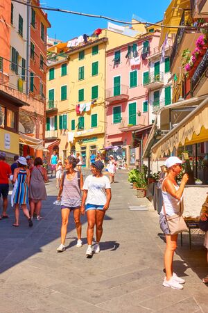 Riomaggiore, La Spezia, Italy - July 2, 2019:  Walking tourists in the old street in Riomaggiore, Cinque Terre