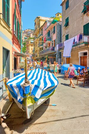 Manarola, Italy - July 2, 2019:  Parked fishing boat and walking people in the main street in Manarola town, Cinque Terre National Park
