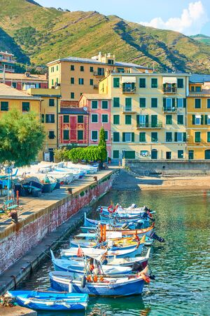 Fishing boats and waterfront with buildings by the sea in Genoa Nervi in the summer evening
