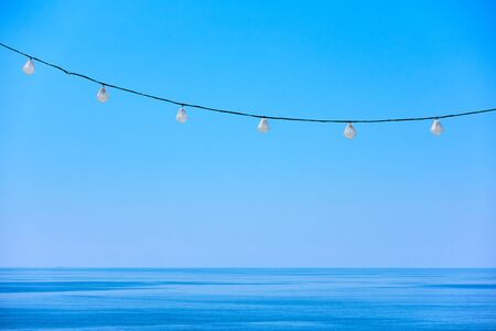 Sea horizon, clear blue sky and decorative string of holiday lights - background with space for text Reklamní fotografie - 129635297