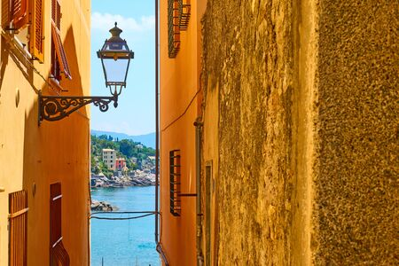 Old street with old street light by the sea in Bogliasco town near Genoa, Italy. Copyspace composition