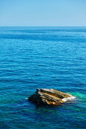 The sea horizon and lonely rock, Liguria, Italy Reklamní fotografie
