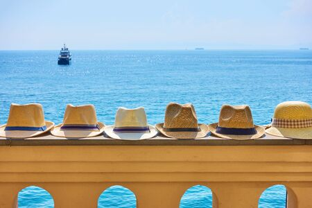 Mans straw sun hats in a row on railing and the sea on sunny day in the background