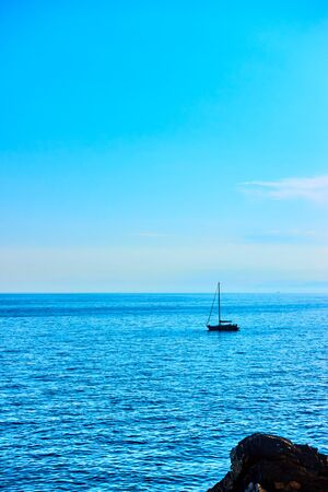 Minimalistic seascape with blue clear sky, sea horizon and small sail yacht. Space for your own text