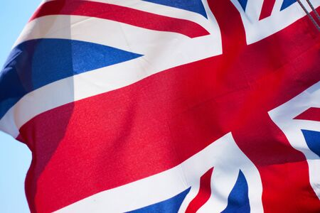 Union Jack - Flag of the United Kingdom waving in the wind close-up Reklamní fotografie - 129634848
