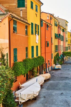 Street with colorful yellow and orange houses in Boccadasse district in Genoa with parked up fishing boats, Italy Stock Photo