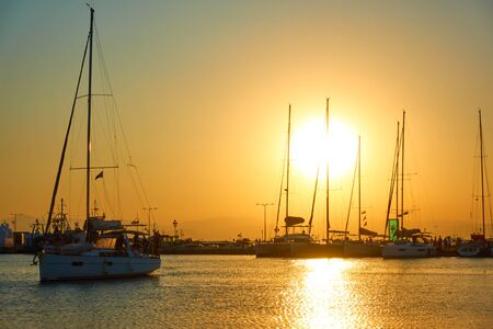 Port of Aegina and silhouettes of yachts at sundown, Saronic Islands, Greece Reklamní fotografie