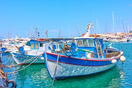 Port of Aegina and old white blue fishing boats on sunny day, Saronic Islands, Greece