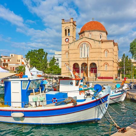 Fshing boats and waterfront with Ekklisia Isodia Theotokou Church on sunny summer day in Aegina town, Saronic Islands, Greece Reklamní fotografie