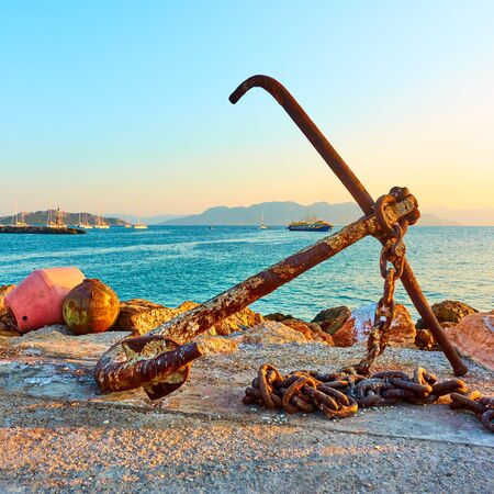Old ship anchor on pier in port of Aegina, Saronic Islands, Greece