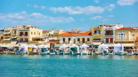 Port and waterfront with small houses in Aegina town on sunny summer day , Saronic Islands, Greece