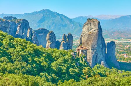 Fantastic panoramic view of Meteora with Rousanou Nunnery on the rock and mountains in the background, Greece -  Picturesque greek scenery