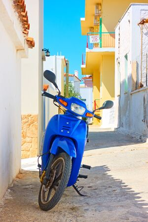 Colorful cosy greek street with parked motor scooter on sunny summer day in Perdika fishing village , Aegina Island, Greece Reklamní fotografie