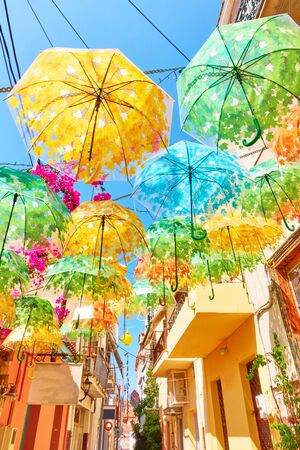 Street decorated with umbrellas of different colours in Aegina town on summer sunny day, Aegina island, Greece Reklamní fotografie