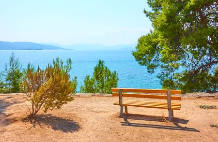 Small garden with bench on the coast in Aegina town on sunny summer day, Aegina Island, Greece - Landscape