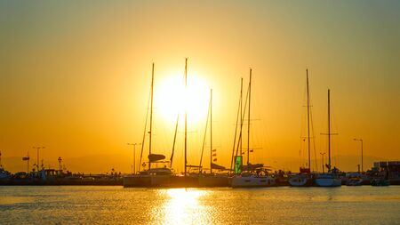 Silhouettes of yachts and boats at sundown at the port of Aegina, Saronic Islands, Greece