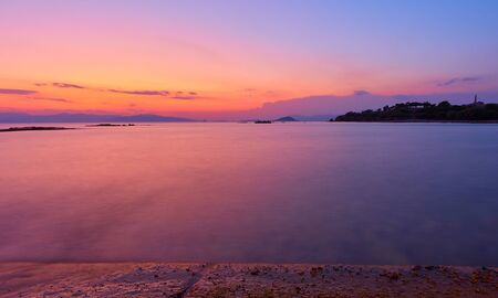 Beautiful sundown over Saronic Gulf of the Aegean Sea in Aegina Island, Greece - Sunset landscape - seascape. Long exposition, the water is totally blurred by motion 写真素材