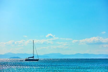 Lonely sail yacht in the sea and blue sky with clouds
