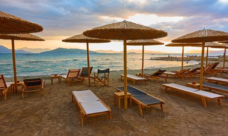 Beach with chaise-longues and straw parasols by the sea at sunset, Aegina Island, Greece. Wide angle panoramic view