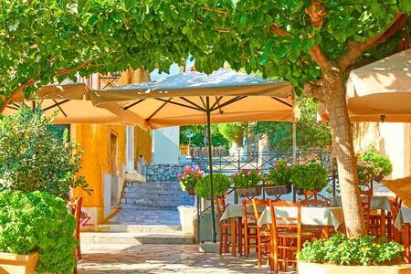 Charming street cafe with tables in a shade of the trees in Plaka district in Athens, Greece 스톡 콘텐츠