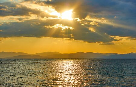 Sundown over the sea and land with mountains on the horizon - Panoramic sunset saescape, landscape