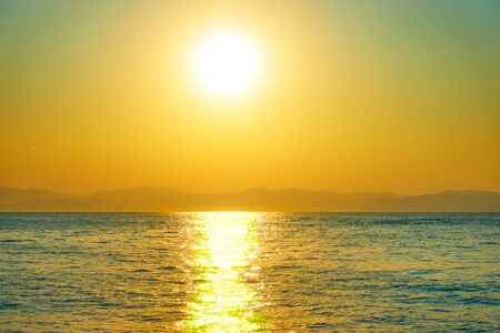 Bright sun over the sea and land with mountains on the horizon - Saescape, landscape