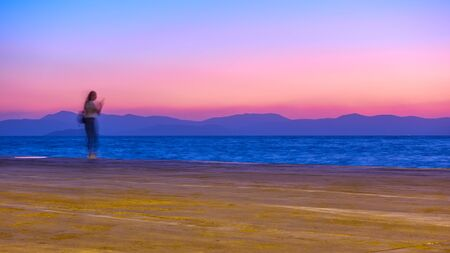 Sunset over Aegean Sea in Aegina Island and a girl on the wharf, Greece, Long exposition, motion blur Reklamní fotografie