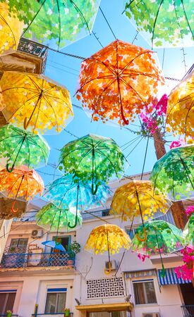 Street decorated with colorful umbrellas in Aegina town on summer sunny day, Aegina island, Greece