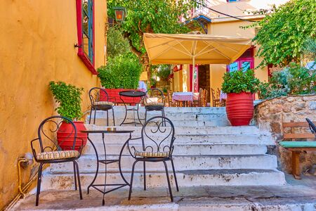 Charming street cafe on the stairs in Plaka district in Athens, Greece