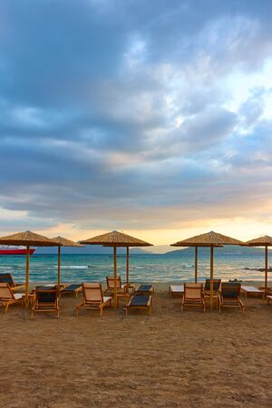 Beach with chaise-longues and straw parasols by the sea at sunset, Aegina Island, Greece. Copyspace composition
