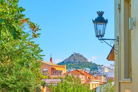 View of Athens city from Plaka district with Mount Lycabettus and vintage street light, Greece - Cityscape