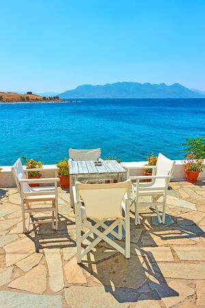 Outdoor cafe with panoramic view at waterfront by the sea  on sunny summer day, Greece - Landscape