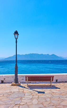 Sea and seaftont with bench and vintage street light ion summer sunny day, Greece - Vertical landscape, seascape