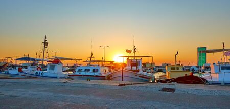 Panorama of the port of Aegina with old fishing boats at sunset, Saronic Islands, Greece