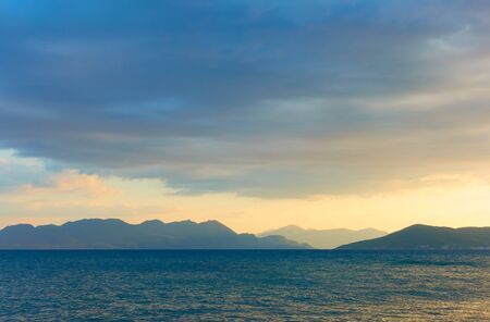 Picturesque view with the sea, clouds and islands on the horizon at dusk -- Sunset seascape - landscape 写真素材