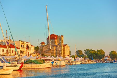 Yachts and waterfront with Ekklisia Isodia Theotokou Church at sunset in Aegina town, Saronic Islands, Greece 写真素材